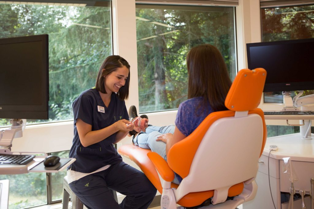 A treatment room at our Kirkland location. An orthodontist showing a girl how to clean teeth on a set of model teeth.