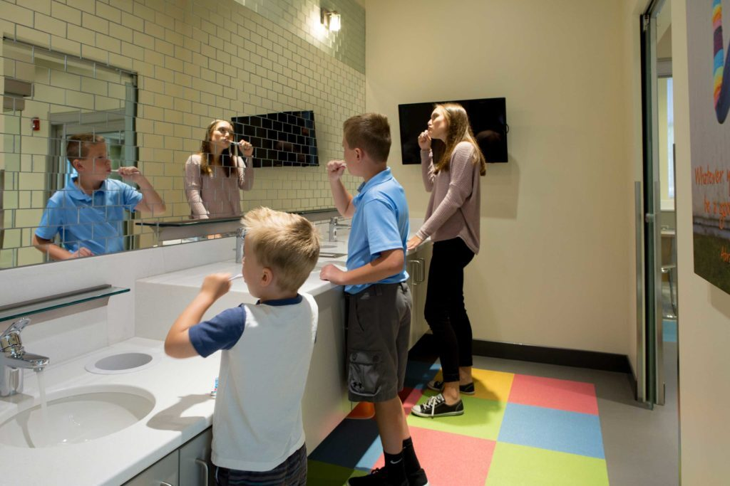 A bathroom with a large mirror. Two young boys and a teenage girl are brushing their teeth.